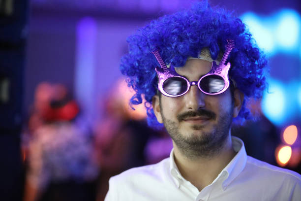 Young man wearing a blue toupee. stock photo