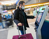 Young man traveler wearing a face mask using self check-in at the airport. Concept for corona virus infection, flu and cold sickness and air pollution.