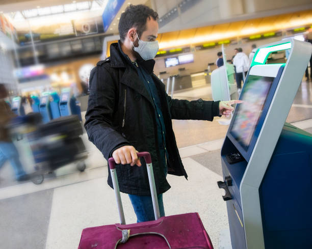 Young man wearing a face mask using self check-in at the airport stock photo