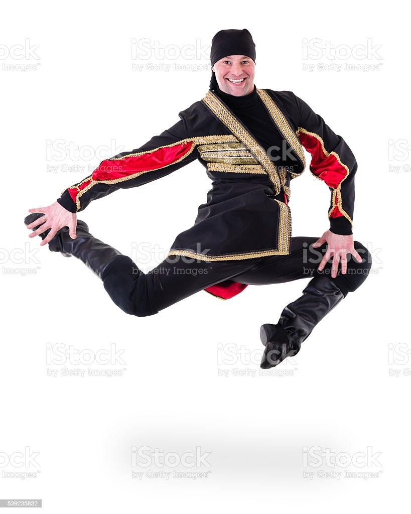young man wearing a folk costume jumping against isolated white stock photo