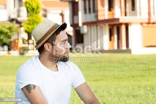 istock Young man wearing a hat and a white T-shirt has a nice weekend 1304232598