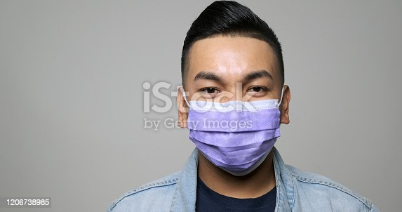 Close up of a Young man wearing a medical mask wearing a medical mask on gray background
