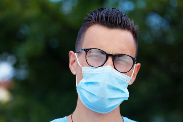 Young man wearing a protective face mask and eyeglasses stock photo