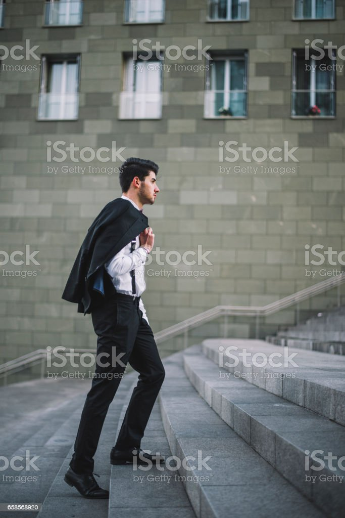 Young man wearing a suit going up stock photo