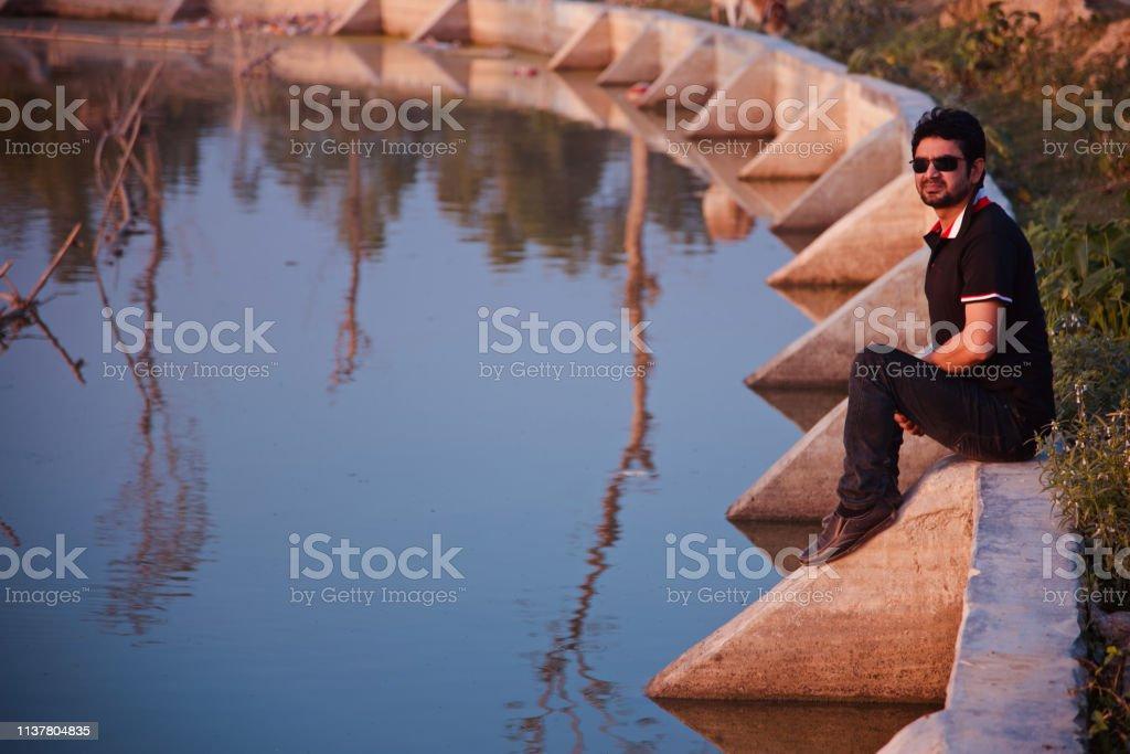 Young man wearing black dress sitting around a lake stock photo