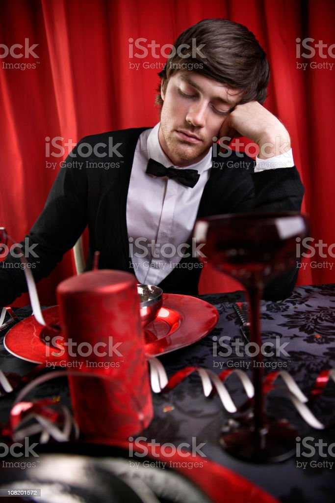 Young Man Wearing Bow Tie Falling Asleep at Party Table royalty-free stock photo