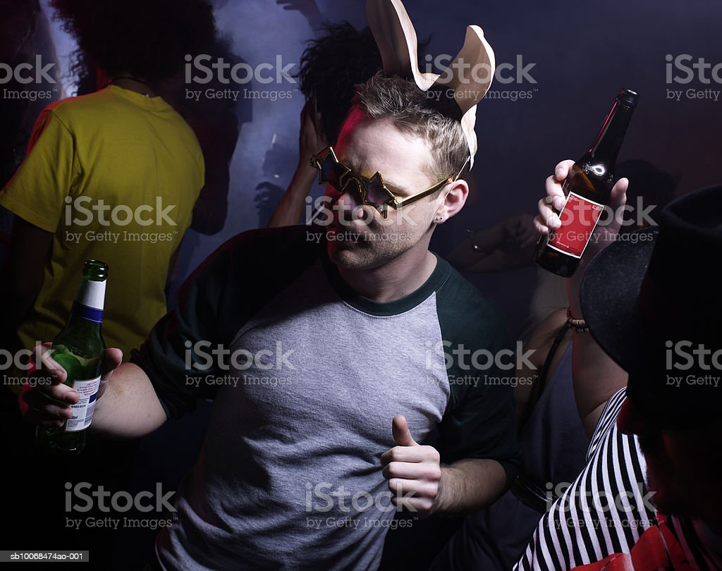 Young man wearing bunny ears, dancing in night club 免版稅 stock photo