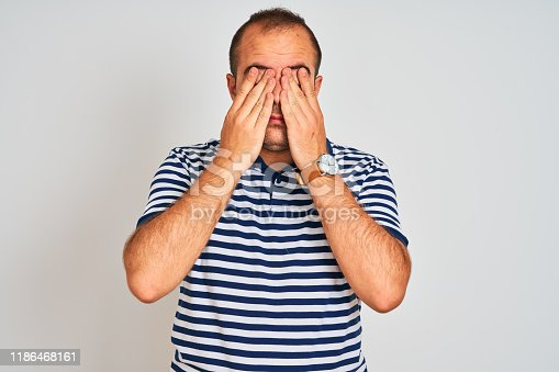 626964348istockphoto Young man wearing casual striped polo standing over isolated white background rubbing eyes for fatigue and headache, sleepy and tired expression. Vision problem 1186468161
