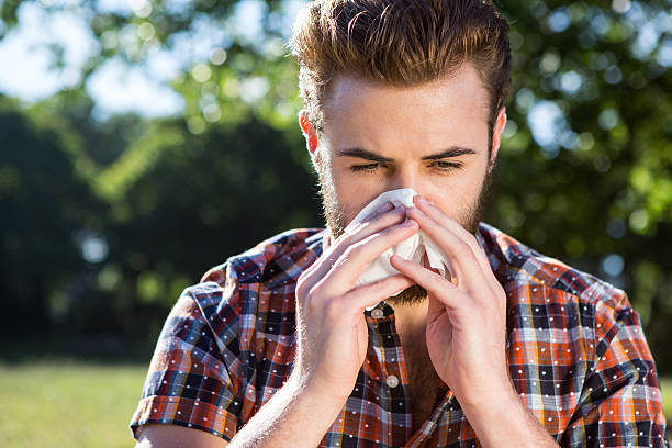 Young man wearing checked shirt blowing his nose with tissue Handsome hipster blowing his nose on a summers day human parainfluenza virus stock pictures, royalty-free photos & images