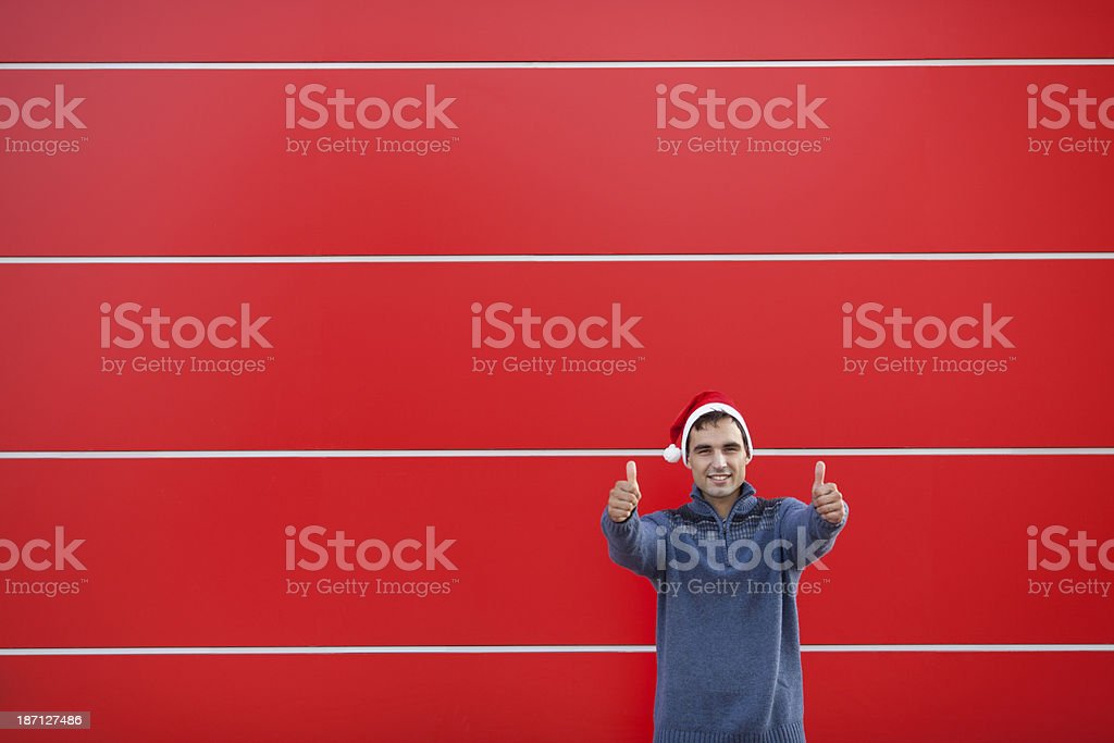 Young man wearing christmas hat and showing thumbs up. royalty-free stock photo