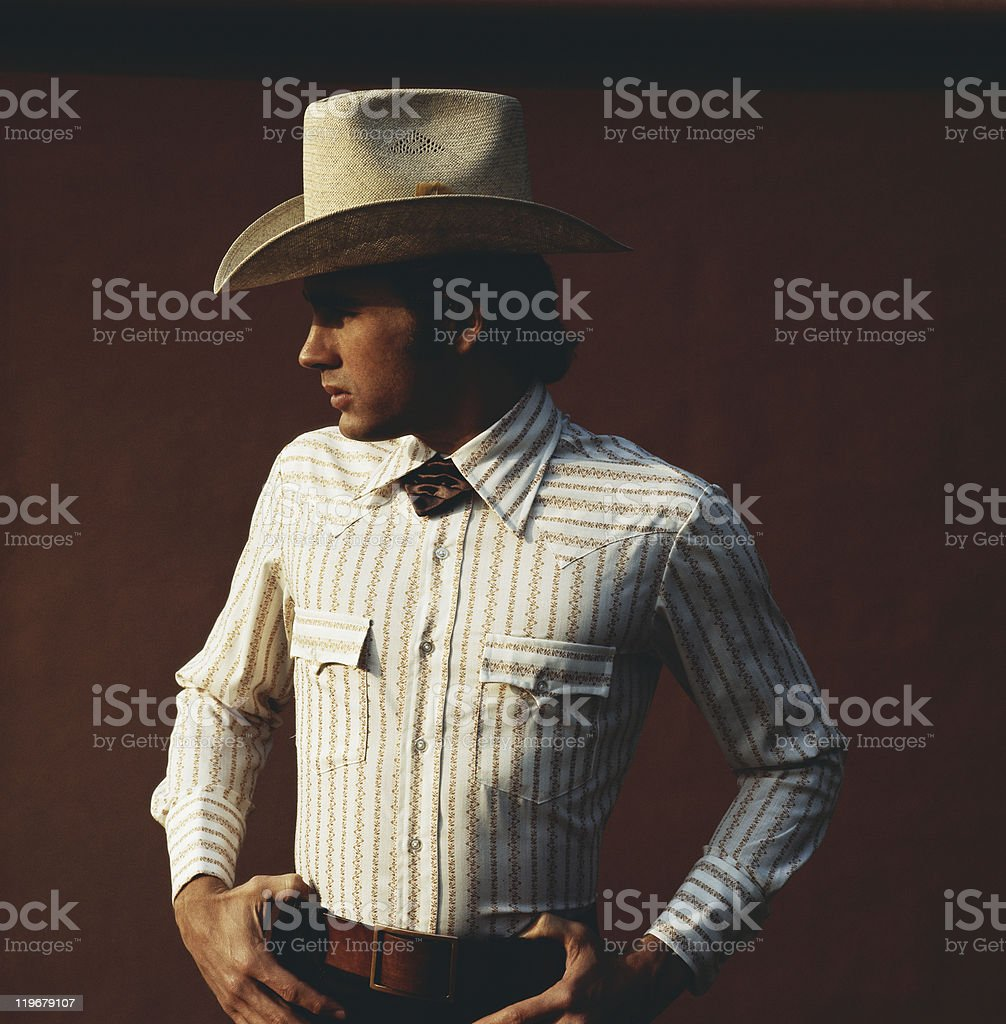 Young man wearing cowboy hat against brown background, close-up stock photo