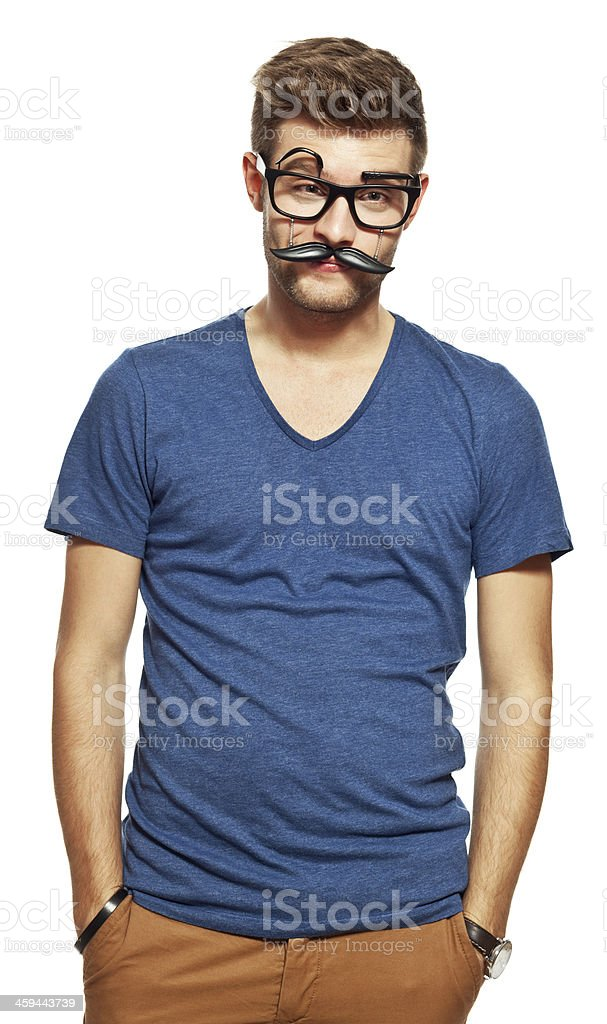 Young man wearing face mask Portrait of young man wearing funny face mask standing with hands in pockets and looking at camera. Studio shot, white background. 20-24 Years Stock Photo
