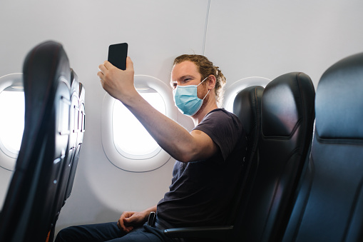 Young man wearing face mask relaxes in airplane