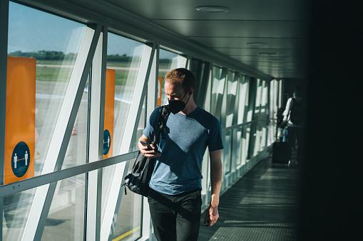 Young man wearing face mask walks through airport