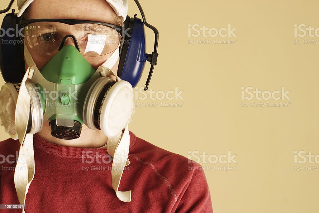 Young man wearing goggles, respirator, and ear muffs stock photo