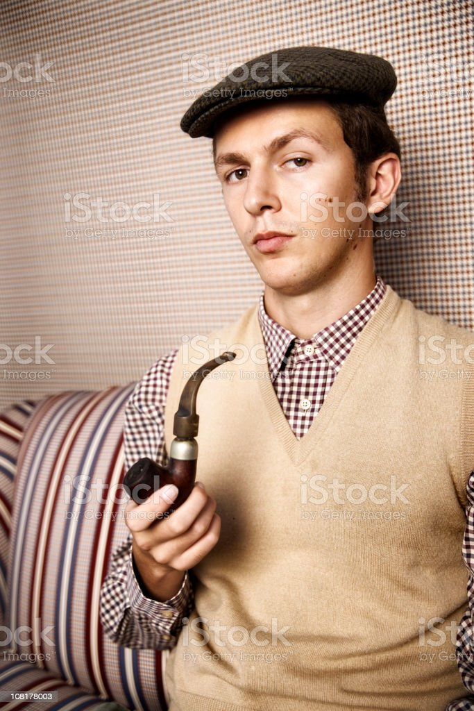 Young Man Wearing Hat and Holding Pipe royalty-free stock photo