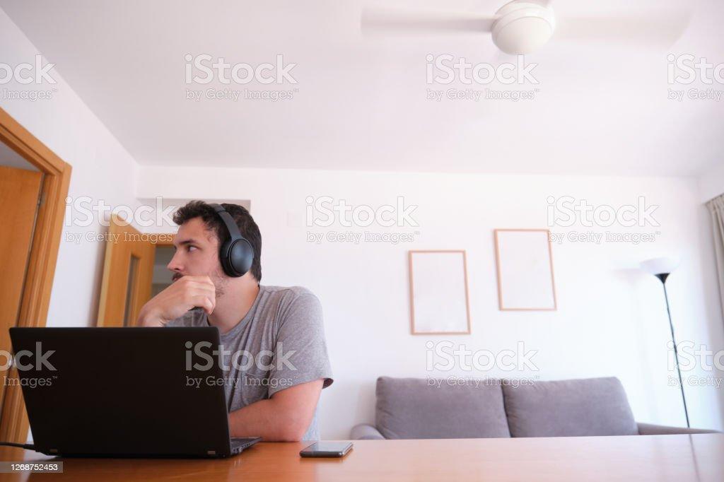 Молодой человек в наушниках отвлекся смотреть сериалы, видео, вместо этого его онлайн-классы - Стоковые фото В помещении роялти-фри