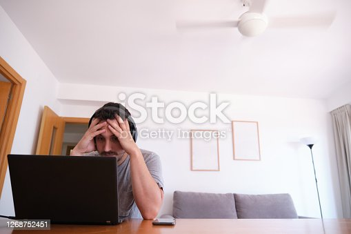 Young man wearing headphones watching series, videos, online classes on a laptop with the fan on. Studying online and e-learning concept.