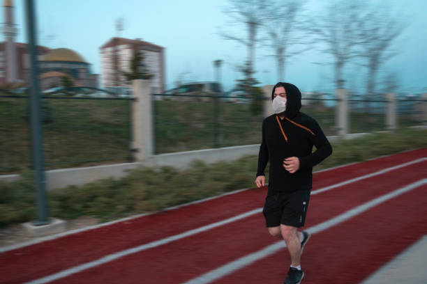 Young man wearing mask and a hoodie running in at a park stock photo