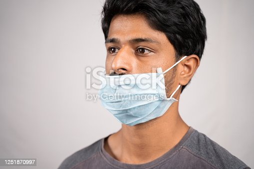young man wearing medical mask below nose - concept showing of improper way of using face masks during coronavirus or covid-19 crisis