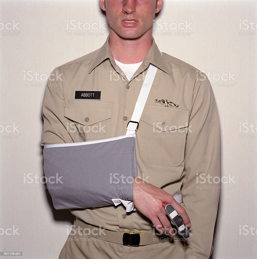Young man wearing military uniform, arm in sling, mid section royalty-free stock photo