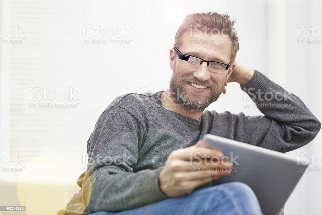 Young man wearing smart glasses with tablet at home stock photo
