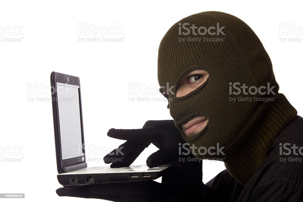 Young man wearing snow mask and posing as computer hacker royalty-free stock photo