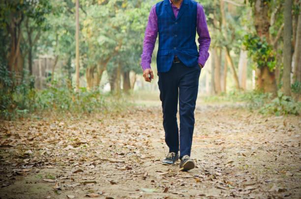 Young man wearing stylish dress walking around a place stock photo