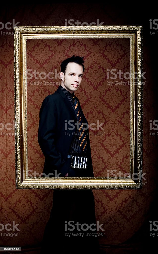 Young Man Wearing Suit and Posing Inside Picture Frame stock photo