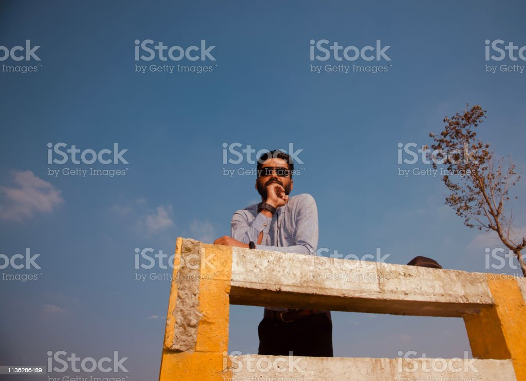 Young man wearing sunglass standing in a place stock photo