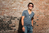 istock Young man wearing sunglasses near red brick wall 476785723