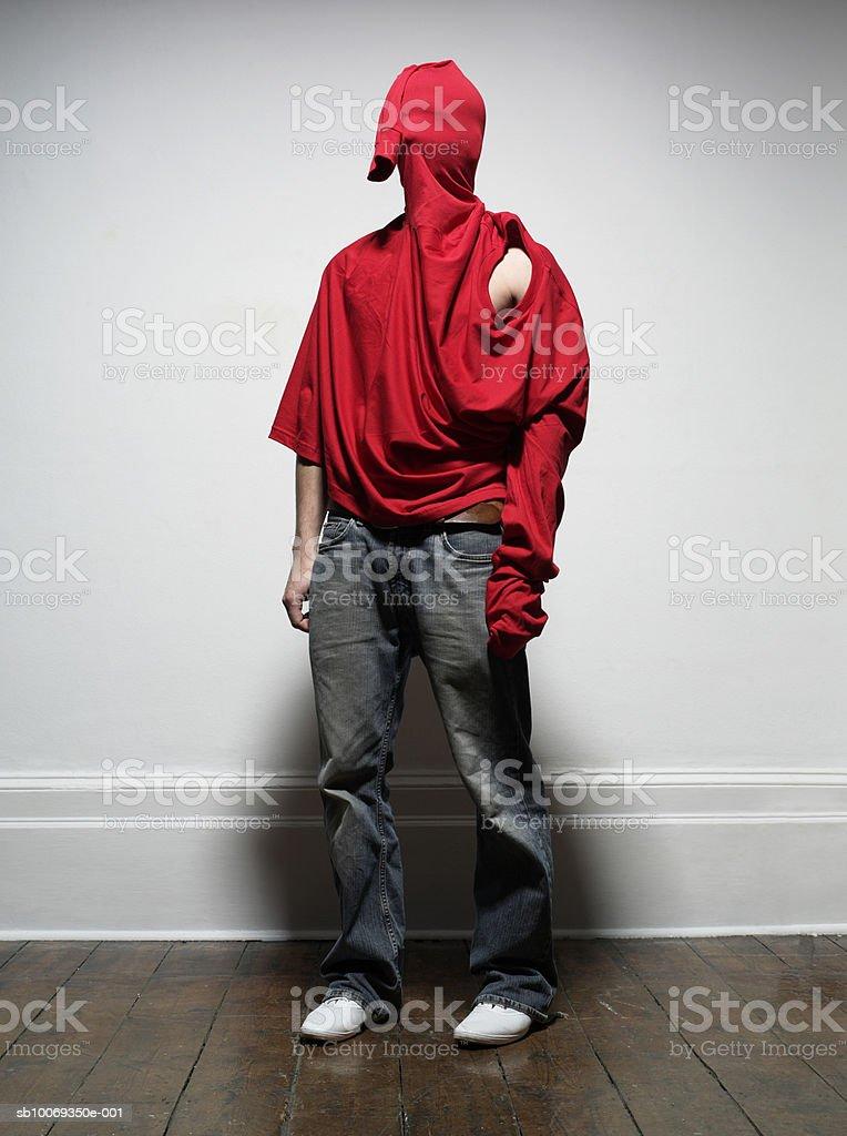 Jovem vestindo Casaco sobre a cabeça, interior foto royalty-free