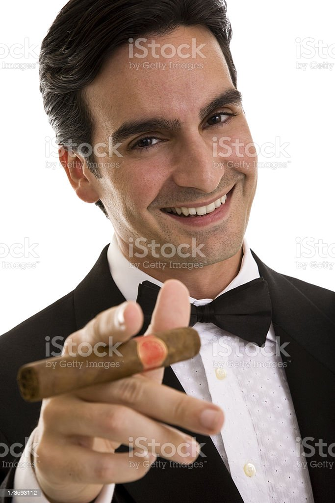 Young man wearing tuxedo holding cigar gesturing towards camera royalty-free stock photo