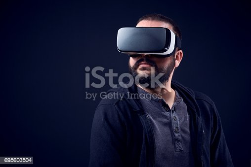 687096686istockphoto Young man wearing virtual reality goggles. Black studio VR concept. 695603504