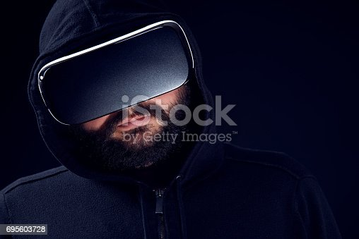 687096686istockphoto Young man wearing virtual reality goggles. Black studio VR concept. 695603728