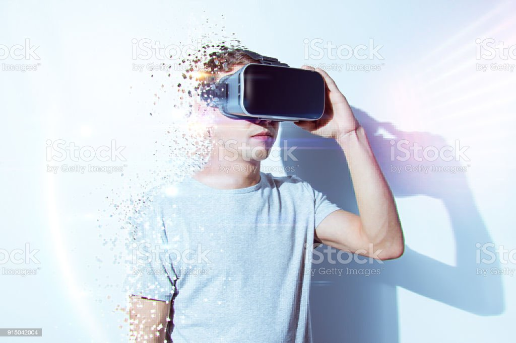 Young man wearing virtual reality goggles in modern coworking studio. Smartphone using with VR headset. Horizontal – zdjęcie