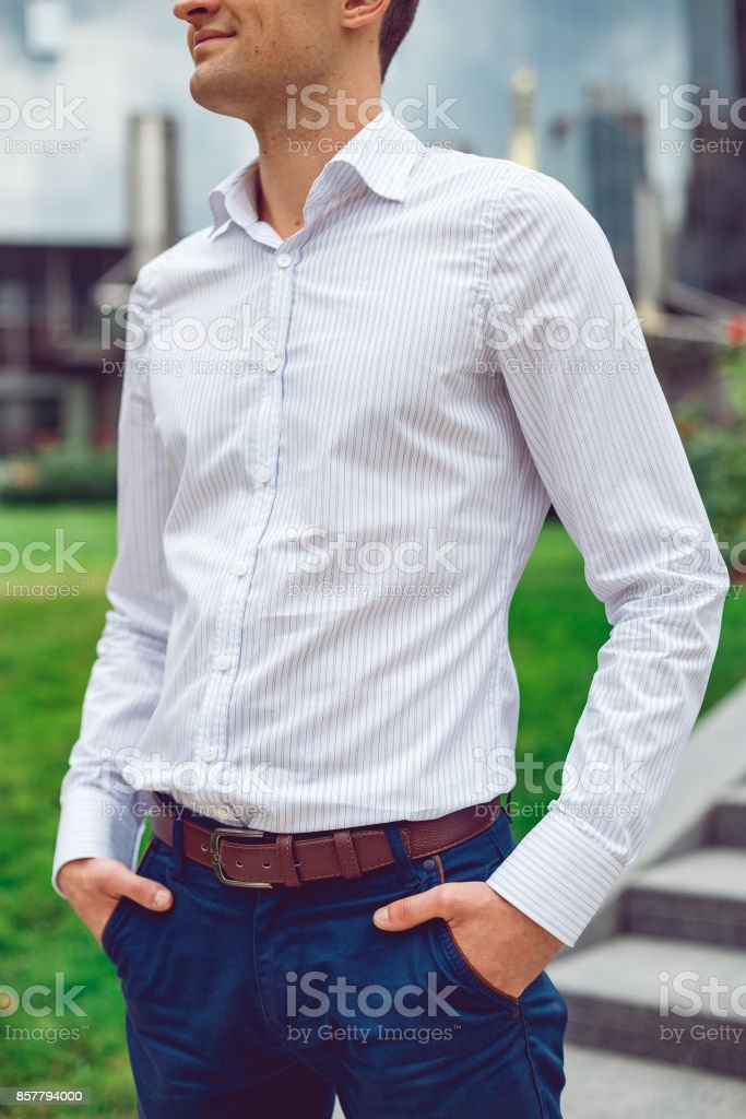 Young man wearing white shirt and blue trousers posing on the street stock photo