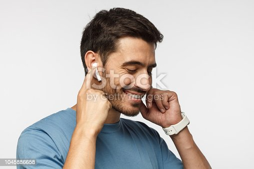 istock Young man wearing wireless earbuds and blue t shirt, listening to his favorite musical album online, touching one earphone to control application 1045886658