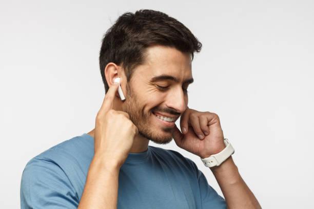 jeune homme portant des écouteurs sans fil et t-shirt bleu, écouter son album de musique préféré en ligne, toucher un écouteur pour l'application de contrôle - écouteurs intra auriculaires photos et images de collection