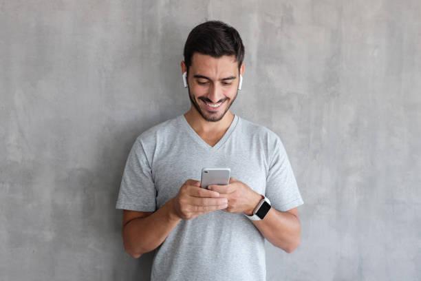jeune homme portant des écouteurs sans fil et montres intelligentes, adossé à un mur texturé gris, en regardant l'écran du smartphone, navigation web et sourit gentiment tout en bavardant - écouteurs intra auriculaires photos et images de collection