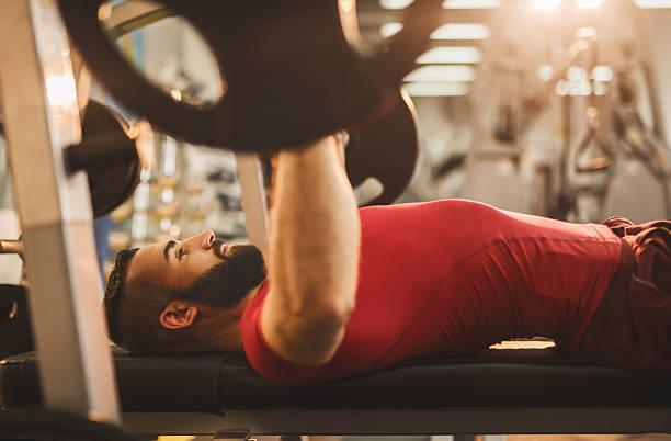 Junger Mann, Gewichtheben auf eine Flachbank im Fitnessraum. – Foto