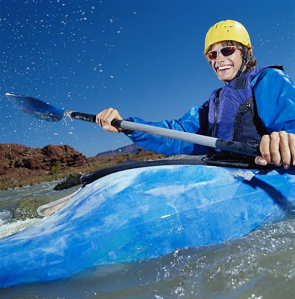Young man white water kayaking, Colorado River, Moab, Utah, USA stock photo