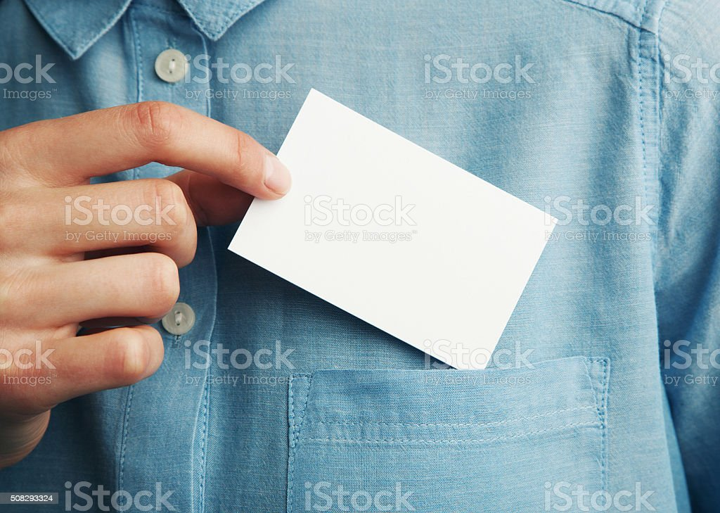 Young man who takes out blank business card from the stock photo