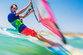 Front view of a young man on a windsurf riding turquoise waves.