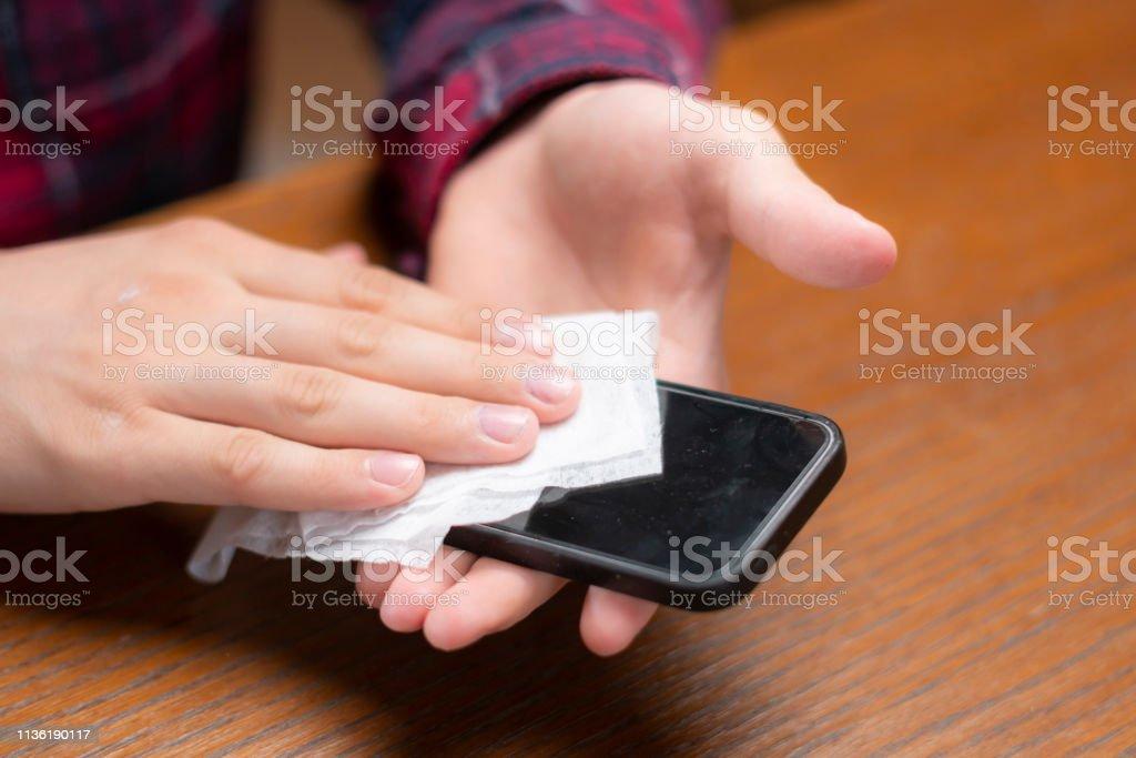 젊은 남자가 젖은 냅킨 그의 가제트 화면을 닦아 - 로열티 프리 감시 스톡 사진