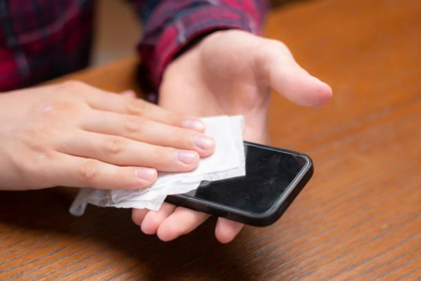 young man wipe his gadgets screen with wet napkin - cleaning zdjęcia i obrazy z banku zdjęć