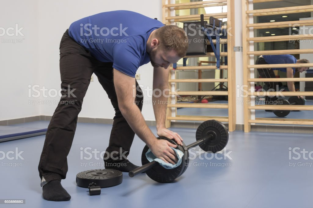 young man wiping cleaning, weights, weight bar stock photo