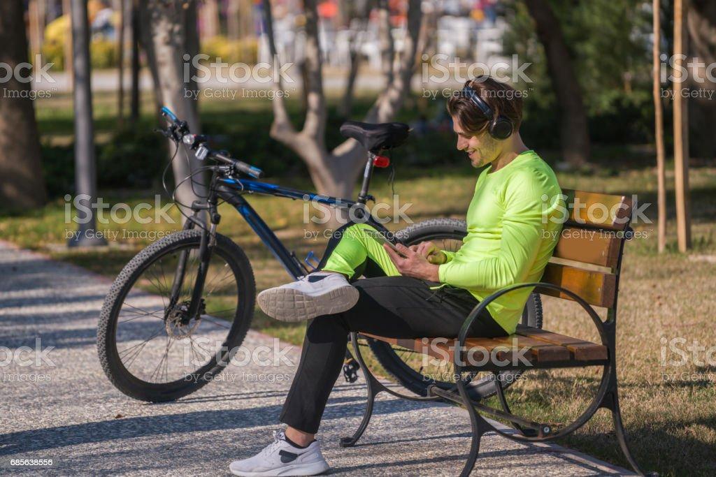 年輕人在公園裡休息的機智自行車 免版稅 stock photo