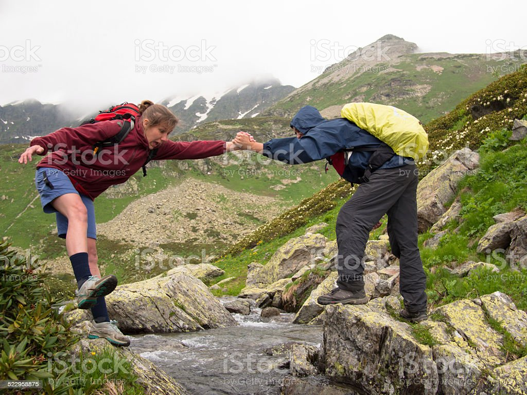 Young man with a backpack helps frightened woman stock photo