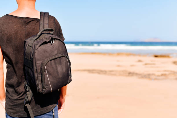 young man with a backpack on the beach stock photo